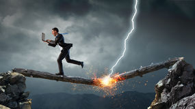 Overcoming fear of failure . Mixed media . Mixed media. Businessman running on broken wooden log above gap. Mixed media royalty free stock photography