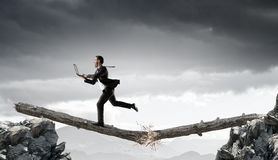 Overcoming fear of failure . Mixed media . Mixed media. Businessman running on broken wooden log above gap. Mixed media stock images