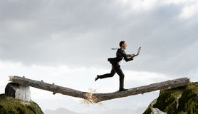 Overcoming fear of failure . Mixed media . Mixed media. Businessman running on broken wooden log above gap. Mixed media royalty free stock images