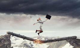 Overcoming fear of failure . Mixed media . Mixed media. Businesswoman jumping on broken wooden log above gap. Mixed media stock photography