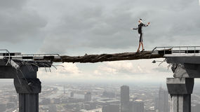 Overcoming fear of failure. Young brave businesswoman with blindfolder on eyes walking on log above gap Stock Photo