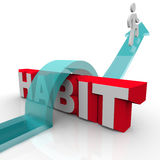 Overcoming a Habit Addiction Person Over Word Obstacle. A man jumps over the word habit on an arrow, illustrating the bravery and courage needed to overcome and Royalty Free Stock Photography