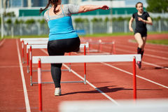 Overcoming hurdles. Rear view of fat woman in sportswear running on stadium and overcoming obstacles Stock Photos