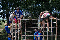 Overcoming  obstacles. Men and women work at overcoming the obstacle of a metal cage at the 2012 mudathlon in indiana Royalty Free Stock Photos