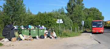 Overcrowded garbage cans next to the bus stop. VILNIUS, LITHUANIA - JULY 23, 2017: Overcrowded garbage cans next to the bus stop. In this Baltic country very Stock Images