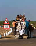 Overcrowded rural transit in India. Workers in the Rann of Kutch district of Gujarat, India, negotiating space on an overcrowded vehicle that will take them to Stock Photo
