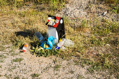 Overcrowded trash. Overcrowded urn on the lawn. Garbage on the grass Stock Images