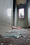 Overdose. A person lying on the floor inn an old worn-out railway carriage with broken glass on the floor Royalty Free Stock Photos
