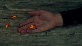 Overdosis - pillen in hand verslaafde die op de vloer liggen stock videobeelden