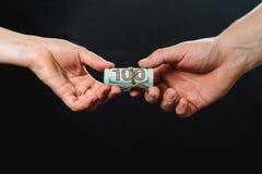 Overdracht die van geld in dollarrekeningen, een steekpenning ontvangen stock fotografie