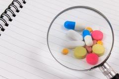 Overdrijf en vele kleurrijke pillen op lege blocnote stock foto's