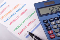 Overdue Bills. A number of overdue household bills with a calculator and a pen Stock Photo