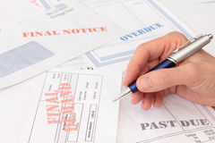 Overdue Bills and Invoices with Pen in Hand Stock Photos