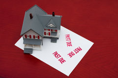 Overdue Mortgage. An overdue bill beside a house on red background, overdue mortgage Royalty Free Stock Image
