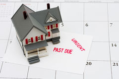 Overdue Mortgage. An overdue bill beside a house on calendar background, overdue mortgage Royalty Free Stock Photo