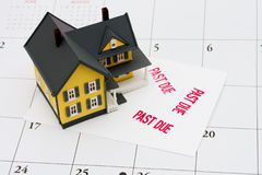 Overdue Mortgage. An overdue bill beside a house on calendar background, overdue mortgage Royalty Free Stock Photography