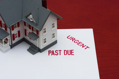 Overdue Mortgage. An overdue bill beside a house on red background, overdue mortgage Royalty Free Stock Images