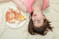 Overeat girl lying. Sad overeat girl lying with pizza pieces Stock Images