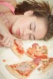 Overeat girl lying. Sad overeat girl lying with pizza pieces Stock Photography