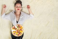 Overeat young woman. Overeat woman with pieces of pizza on white background Stock Photo