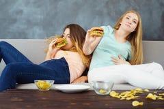 overeaten les femmes s'asseyant avec un bon nombre de prêt-à-manger photo libre de droits