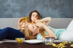 Overeatenvrouwen die bij bus liggen die snel voedsel eten stock fotografie