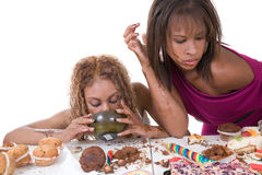 Overeating. Two black girls in a horrible food binge Stock Photography