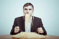 Overeating. And consumerism concept. Silly nasty businessman eating pasta Stock Photos