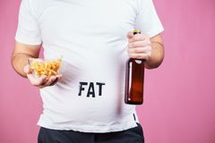 Overeating, fast food, glutton, alcohol addiction. Overeating, fast food, excess food, glutton, alcohol addiction, junk food. Fat obese man with bottle of beer stock photo