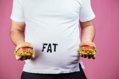 Overeating, fast food, glutton, junk food. Overeating, fast food, excess food, glutton, junk food. Fat obese man with two hamburgers stock photo