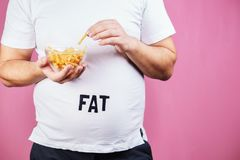 Overeating, fast food, glutton, junk food. Overeating, fast food, excess food, glutton, junk food. Fat obese man with portion of french fries royalty free stock images