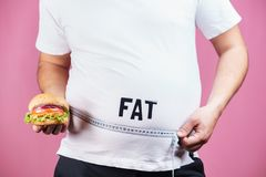 Glutton, junk food, diet, fast food, overeat. Overeating, fat food, glutton, junk food. Fat obese man with hamburger and measure tape royalty free stock image