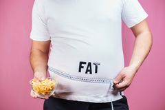 Overeating, fat food, glutton, junk food. Fat obese man with french fries and measure tape stock image