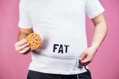 Overeating, glutton, sugar addiction, junk food. Fat obese man with burger and measure tape stock photo