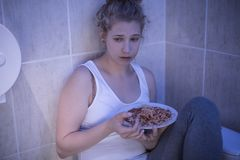 Overeating sad girl. Picture of overeating sad girl sitting in bathroom Royalty Free Stock Image