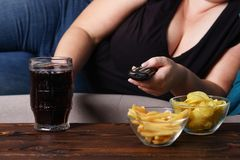 Overeating, sedentary lifestyle, alcohol addiction. Overeating, sedentary lifestyle, bad habits, food addiction, eating disorders. fat overweight woman lay on stock image