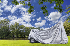overed golf car parking on green grass with beautiful sky backgr Stock Image
