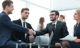 Overeenkomst besluiten en partners die dient de aanwezigheid van teamleden de schudden in royalty-vrije stock foto