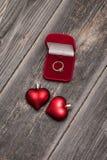 Overeenkomsten smaragdgroene ring en rode harten Stock Afbeelding