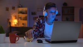 Overemotional nastoletnia bawić się gra komputerowa na laptopie i jeść przekąskach, nałóg zbiory wideo