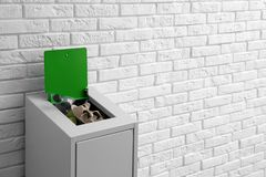 Overfilled trash bin near wall, space for text. Recycling concept. Overfilled trash bin near brick wall, space for text. Recycling concept royalty free stock photography
