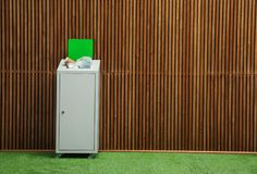 Overfilled trash bin near wooden wall indoors, space for text. Recycling concept royalty free stock image