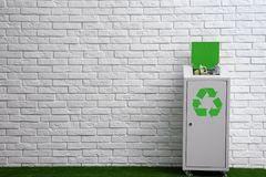 Overfilled trash bin with recycling symbol near wall indoors. Space for text. Overfilled trash bin with recycling symbol near brick wall indoors. Space for text stock image