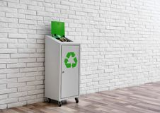 Overfilled trash bin with recycling symbol near wall indoors. Space for text. Overfilled trash bin with recycling symbol near brick wall indoors. Space for text royalty free stock image
