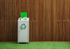 Overfilled trash bin with recycling symbol near wall indoors. Space for text. Overfilled trash bin with recycling symbol near wooden wall indoors. Space for text royalty free stock photos