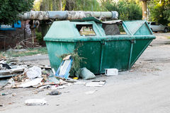 Overfilled trash dumpster in ghetto neigborhood outdoors Royalty Free Stock Photography