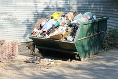 Overfilled trash dumpster in ghetto neigborhood in Stock Photos
