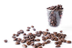 Overflow coffee beans. From transparent cup on isolated white background Royalty Free Stock Images