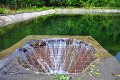 Overflow drain on lake Royalty Free Stock Photo
