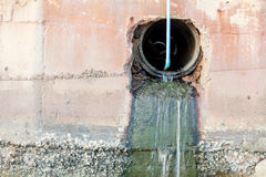 Overflow  water pipe. Stone wall background Royalty Free Stock Image